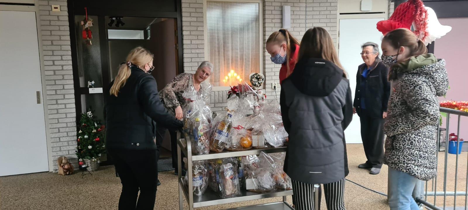 Meidenvoetbalteam RVLC MO13, brengen eigengemaakte kerstpakketten naar bewoners van de Scharleijen te St. Nicolaasga.